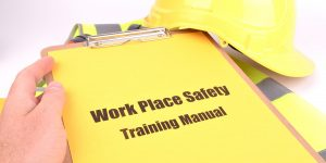 A yellow work place training safety manual held by a safety officer with a yellow hard hat in the background
