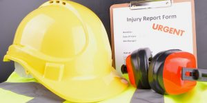 Injury report form with a yellow hard hat and ear muffs on top of a yellow high visibility vest.